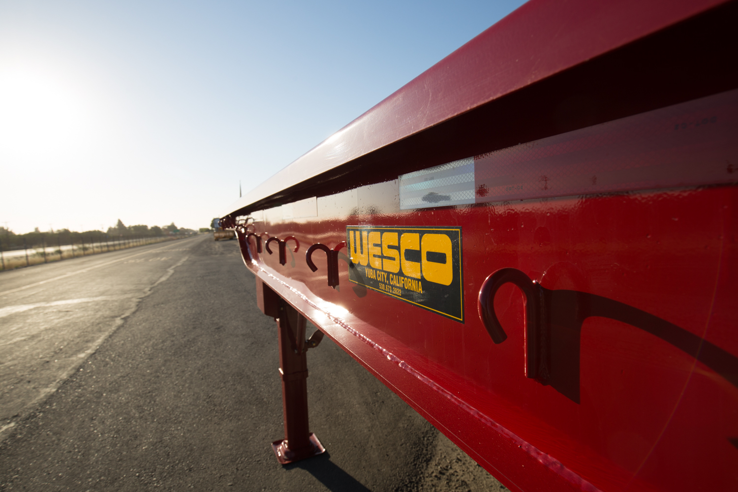red wesco flatbed on a road at sunrise
