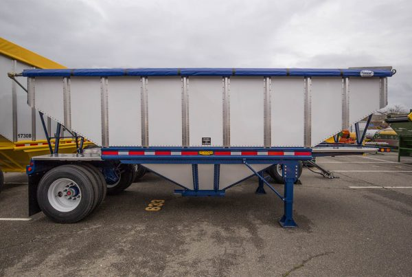 blue and white hopper trailer in a parking lot