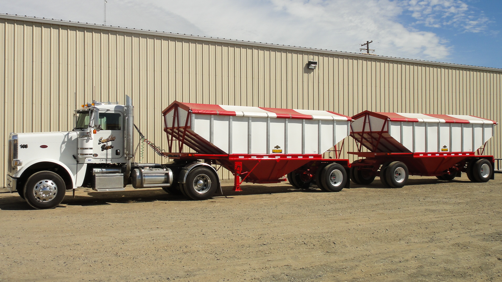 red hopper trailer set pulled by white truck